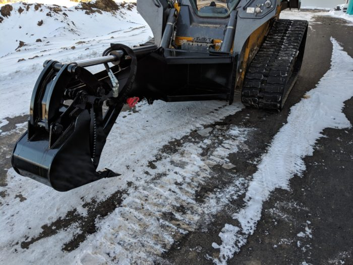 A backhoe attachment excavating during winter